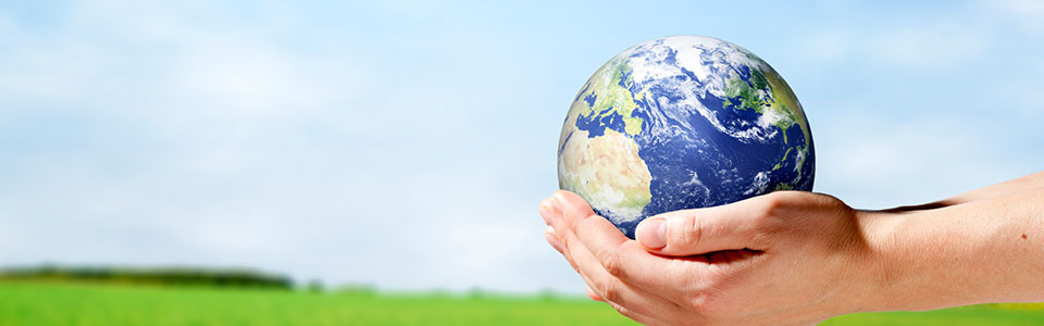 A hand holding out a ball-sized Earth in front of a light blue background.