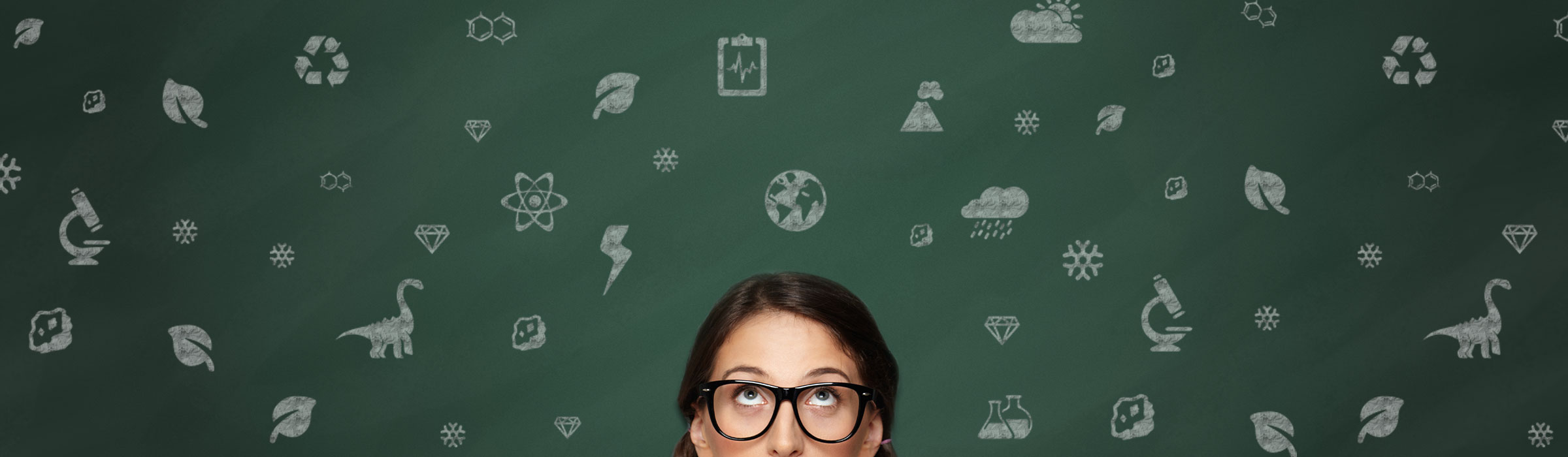 A brunette woman wearing glasses looking up at the science symbols spread around the green background; microscopes, volcanos, snowflakes, atoms, clouds, dinosaurs.